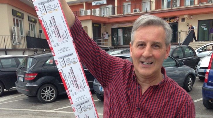 Un tifoso mostra fiero i biglietti appena uscito dalla sede